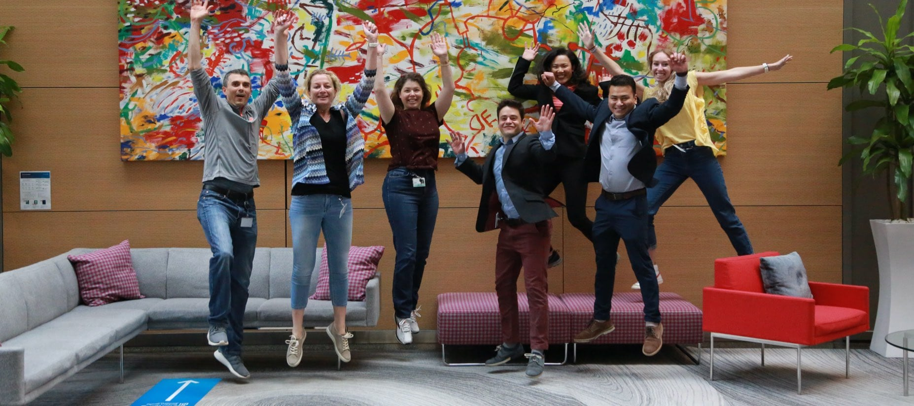 group of 7 people in a lobby in front of a colorful abstract painting, jumping in the air and smiling